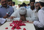 A Pakistani man mourns over the coffin of a relative killed in a plane crash in Pakistan, at a hospital in Islamabad on Saturday. Pakistan barred the head of the airline from leaving the country as it began a probe into the disaster that sparked anger among distraught relatives. The Bhoja Air flight from Karachi came down on Friday evening, killing all 127 people on board