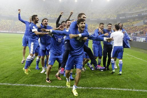 The Greece team celebrate after defeating Romania in their World Cup qualifying playoff second leg match at the National Arena in Bucharest, Tuesday, Nov. 19, 2013