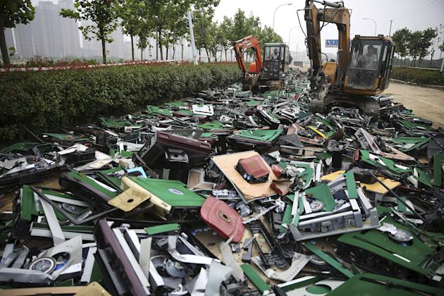 Excavators smash and run over seized automatic mahjong tables during a campaign against gambling in Hefei