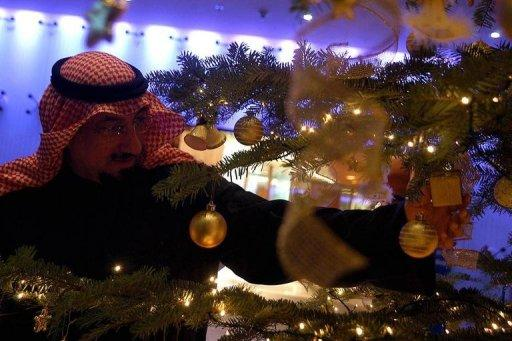 A Kuwaiti man looks at a Christmas tree displayed at a Kuwaiti resort, south of Kuwait City, on December 16, 2004. Several Kuwaiti liberal civil societies have condemned calls from some organisations and individuals forbidding the celebration of Christmas in the oil-rich Gulf state, a report said Sunday