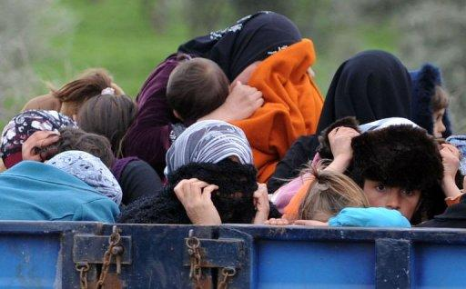 Syrian refugees hide their face as they arrive near the border between Syria and Turkey at Reyhanli in Antakya. All six Arab Gulf states will close their embassies in Syria in protest at the year-long crackdown in the country, said Gulf Cooperation Council (GCC) head Abdullatif al-Zayani early Friday