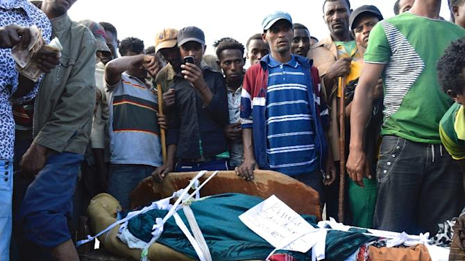 People in Wolenkomi, some 60km west of Ethiopia's capital Addis Ababa stand on December 15, 2015 near the body of a protester from Ethiopia's Oromo group allegedly shot dead by security forces