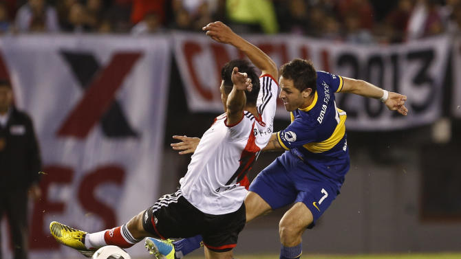 Boca Juniors' Juan Manuel Martinez , right, shoots past River Plate's Ariel Rojas , left, during an Argentina's league soccer match in Buenos Aires, Argentina, Sunday, Oct. 6, 2013