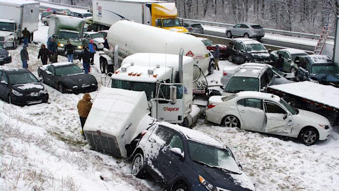 Vehicles are piled up at mile marker 286 on the Pennsylvania Turnpike, a mile outside Reading, Pa., on Thursday, Dec. 26, 2013. Portions of both the Pennsylvania Turnpike and Interstate 78 were shut down in snowy eastern Pennsylvania Thursday after chain-reaction pileups involved dozens of vehicles on slippery roads. (AP Photo/David C. Ronk)