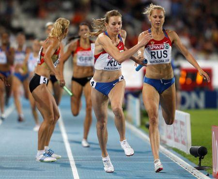 Russia's  Firova receives the baton from Ustalova during the women's 4 x 400 metres relay final at the European Athletics Championships in Barcelona