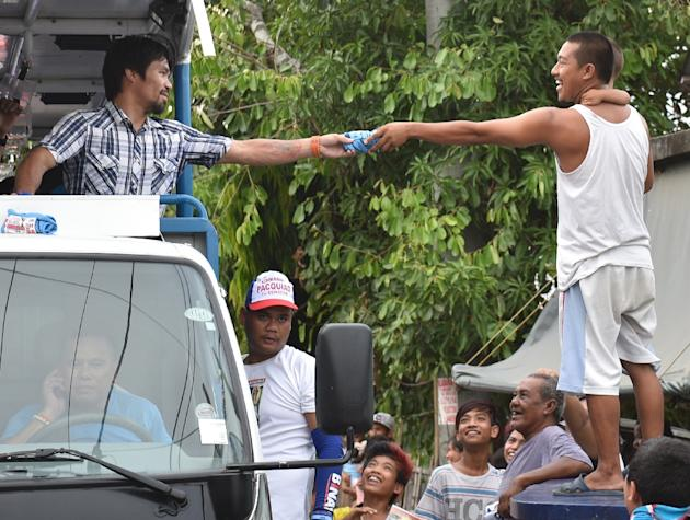 Boxing legend Manny Pacquiao smiles as he soaks up the sounds of adoring fans screaming his name, their cheers heralding a new career as one of the Philippines' most powerful politicians