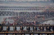 Hindu devotees gather on the shores of the River Ganges as it meets the Yamuna river (background) in Allahabad, on February 9, 2013. Tens of millions of Hindu pilgrims are preparing to cleanse their sins with a plunge into the sacred River Ganges, ahead of the most auspicious day of the world's largest religious festival