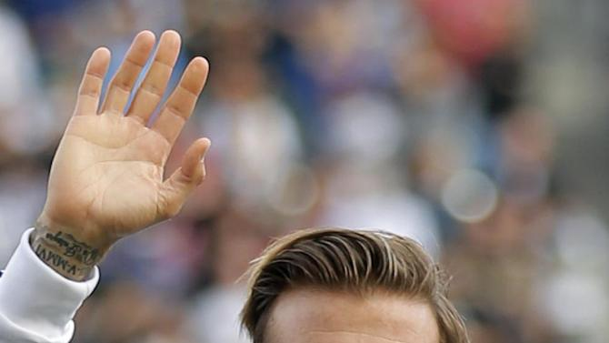 FILE- Los Angeles Galaxy's David Beckham, of England, waves as he stands with his son Romeo, in Carson, Calif., USA, in this file photo dated Saturday, Dec. 1, 2012.  It is announced Tuesday Dec. 18, 2012 that the son of soccer star David Beckham and former Spice Girl singer Victoria Beckham, ten-year old Romeo Beckham, is the new face of the London based clothing brand Burberry and will feature in upcoming ads for Burberry's spring/summer 2013 collection. (AP Photo/Jae C. Hong, FILE)