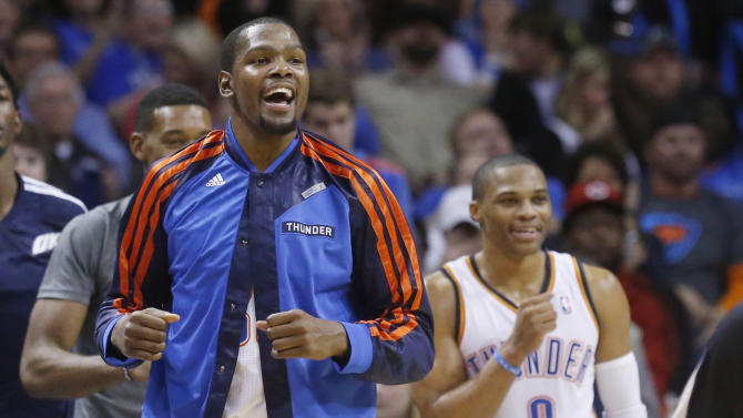 Oklahoma City Thunder forward Kevin Durant, left, and guard Russell Westbrook (0) cheer from the bench in the third quarter of an NBA basketball game against the San Antonio Spurs in Oklahoma City, Wednesday, Nov. 27, 2013. Oklahoma City won 94-88