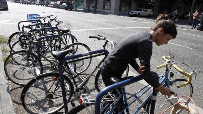 Deanna Horton locks up her bike in downtown Portland, Ore., Wednesday, Sept. 19, 2012.  Researchers at Portland State University found that Portland is a magnet for the young and college educated, even though a disproportionate share of them are working in part-time jobs or positions that don't require a college degree. (AP Photo/Don Ryan)