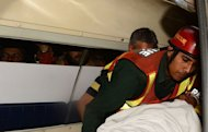 Pakistani politician and former cricketer Imran Khan is carried by rescuers to hospital in Lahore on May 7, 2013, after he fell off a lift taking him onto a stage at an election rally