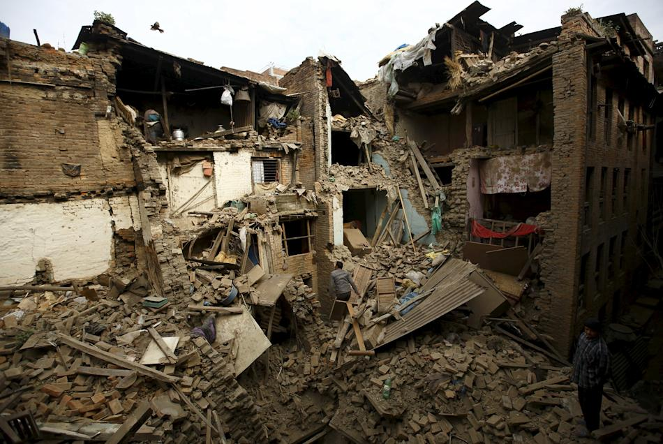 People search for family members trapped inside collapsed houses a day after an earthquake in Bhaktapur