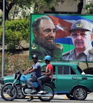 "A poster of Cuban President Raul Castro (R) and former leader Fidel Castro in Santiago de Cuba in March 2012. Cubans, many of whom openly consider themselves ""Fidelistas"" even as they denounce the shortcomings of the communist regime, believe their former leader spends his time in retirement on his property in west Havana, writing his memoirs and occasionally receiving foreign diplomats"
