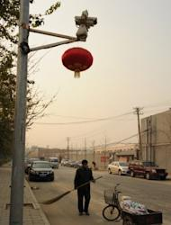 """A Chinese road sweeper works under a surveillance camera watching Ai Weiwei's studio in Beijing. The dissident Chinese artist was barred from a hearing Wednesday challenging a multi-million-dollar tax order against a firm he founded, he said, accusing authorities of trying to """"crush"""" him"""