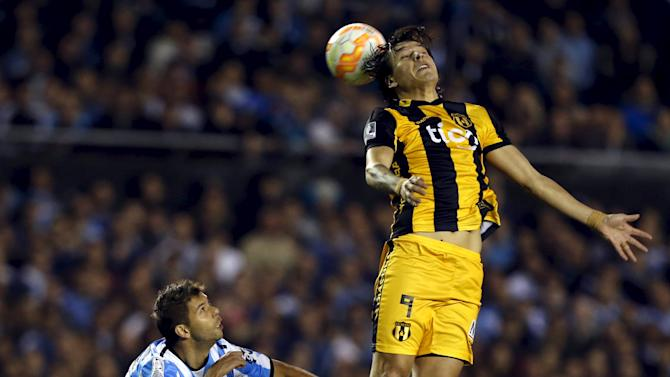 Santander of Paraguay's Guarani jumps for header next to Grimi of Argentina's Racing Club during Copa Libertadores quarter-final second leg soccer match in Buenos Aires
