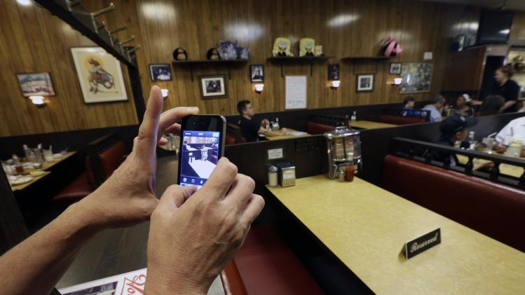 "Liz O'Neil, of Montclair, N.J., takes a photograph of a reserved booth where the last show of the HBO series ""The Sopranos"" was filmed at Holsten's ice cream parlor, Wednesday, June 19, 2013, in Bloomfield, N.J. The sign was put on the booth where the last scene was filmed in honor of actor James Gandolfini who died Wednesday in Italy. He was 51. (AP Photo/Julio Cortez)"