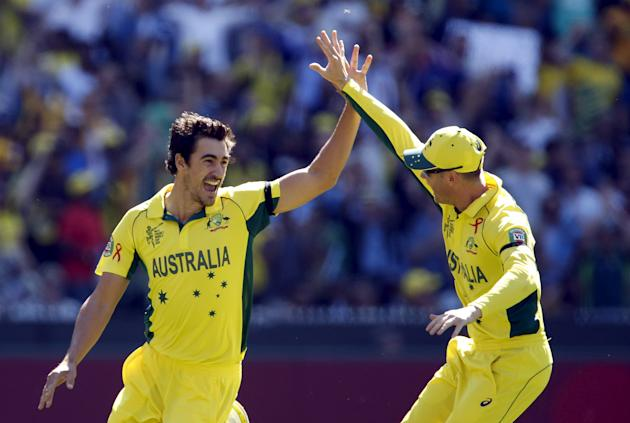 Australia's Mitchell Starc celebrates with captain Michael Clarke after bowling New Zealand's captain Brendon McCullum for a duck during their Cricket World Cup final match at the MCG