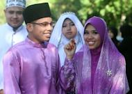 Newly wed couple smiles during their wedding in Selangor near Kuala Lumpur on Saturday. A group of Malaysian Muslim women say they will fight divorce, domestic violence and other problems - by appealing to wives to be more obedient