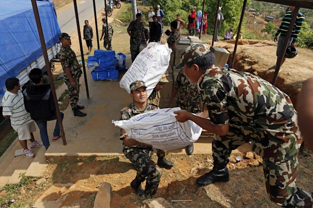 Nepalese soldiers load U.S. AID relief sacks at a staging area near Saturday's massive earthquake's epicenter in the town of Gorkha, Nepal, Tuesday, April 28, 2015. Preparing to make a push in