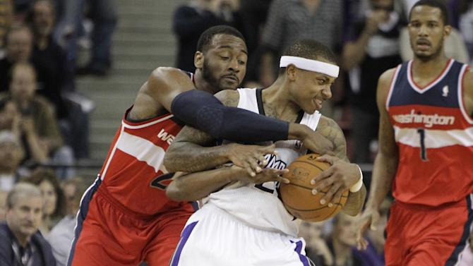 Sacramento Kings guard Isaiah Thomas, center, is fouled by Washington Wizards guard John Wall during the overtime of an NBA basketball game in Sacramento, Calif., Tuesday, March 18, 2014.  The Kings won in overtime 117-111