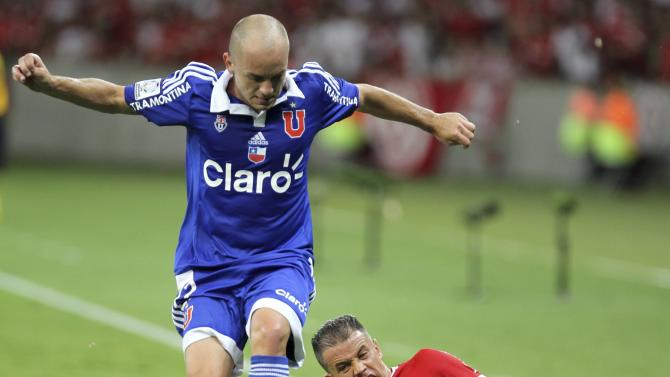 Gustavo Lorenzetti of Chile's Universidad de Chile is tackled by D'Alessandro of Brazil's Internacional during their Copa Libertadores soccer match in Porto Alegre