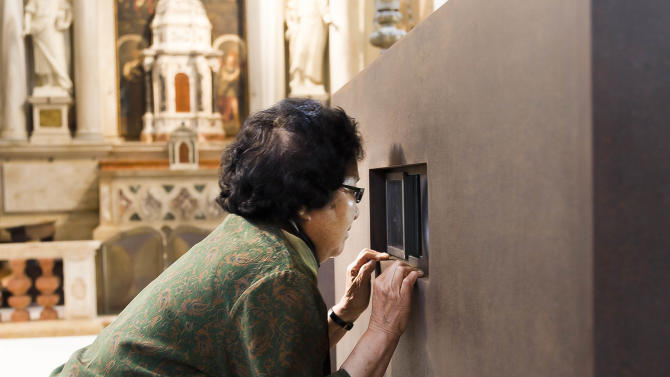 Chinese artist Ai Weiwei's mother Gao Ying looks into one of the six containers part of an installation by her son during a press preview of the 55th edition of the Venice Biennale of Arts in Venice, northern Italy, Tuesday, May 28, 2013. The work on display is called S.A.C.R.E.D. The four initials standing for supper, accuser, cleansing, ritual, entropy and doubt, and referring to Ai Weiwei time 81 days in detention in 2011. Chinese artist Ai Weiwei has been prevented by Chinese authorities from traveling to Venice for the opening of two new works on the sidelines of the Biennale contemporary art show, so his mother came instead. Weiwei's elderly mother, Gao Yng, on Tuesday viewed for the first time a series of dioramas depicting six episodes of pressure during her son's 81 days in detention in 2011. (AP Photo/Domenico Stinellis)