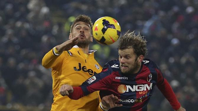 Juventus' Fernando Llorente, left, and Bologna defender Mikael Antonsson, of Sweden jump for the ball during the Serie A soccer match between Bologna and Juventus at the Dall' Ara stadium in Bologna, Italy, Friday, Dec. 6, 2013