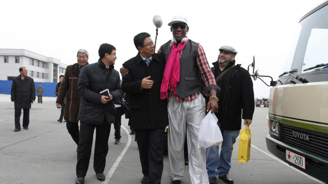 Former NBA basketball star Dennis Rodman, second right, walks with North Korea's Sports Ministry Vice Minister Son Kwang Ho, third right, upon his arrival at the international airport in Pyongyang, North Korea, Monday, Jan. 6, 2014. Rodman took a team of former NBA players on a trip for an exhibition game on Kim Jong Un's birthday, Wednesday, Jan. 8. (AP Photo/Kim Kwang Hyon)