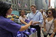"This Wednesday, Aug. 8 2012 photo shows Diana Hunter, left, handing out free vibrators by Trojan to Simon Reed, center, during a promotional giveaway in New York. While Trojan has been selling vibrators since 2009, first-quarter sales this year, around the time the ""Fifty Shades of Grey"" books hit it big, were up about 14 percent from the same quarter a year before, according to Nielsen. (AP Photo/Mary Altaffer)"