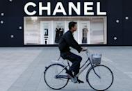 A Chinese man cycles past a luxury boutique in Beijing on October 22, 2009. China's stated aim to narrow the income gulf between its sports-car driving elite and vast numbers who still live in poverty will need radical political and economic changes to work, say economists