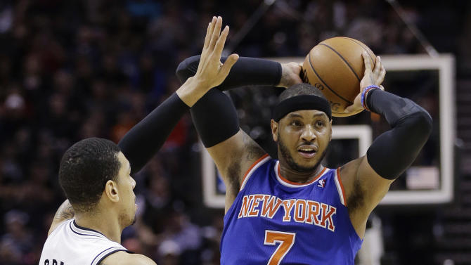 New York Knicks' Carmelo Anthony (7) looks to pass away from San Antonio Spurs' Danny Green (4) during the second half on an NBA basketball game, Thursday, Jan. 2, 2014, in San Antonio. New York won 105-101