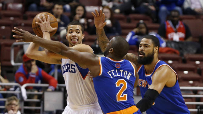 Philadelphia 76ers' Michael Carter-Williams, left, tries to keep the ball away from New York Knicks' Raymond Felton, center, and Tyson Chandler during the first half of an NBA basketball game, Friday, March 21, 2014, in Philadelphia