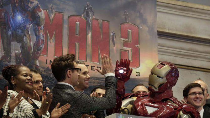 "Actor Robert Downey Jr. gives a high-five to his ""Iron Man"" character during opening bell ceremonies of the New York Stock Exchange, Tuesday, April 30, 2013. Stock prices are opening mostly lower on Wall Street as weak earnings from Pfizer and other companies drag down major market averages.  Downey's film, ""Iron Man 3,"" also starring Don Cheadle and Gwyneth Paltrow, opens nationwide on May 3. (AP Photo/Richard Drew)"