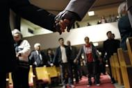 Mourners hold hands during a vigil for victims of the Oikos University shootings at the Allen Temple Baptist Church on April 3, 2012 in Oakland, California