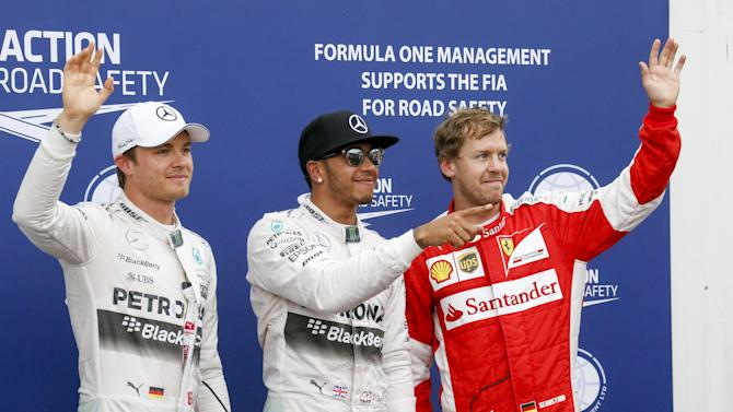 Mercedes Formula One drivers Hamilton of Britain and Rosberg of Germany with Ferrari Formula One driver Vettel of Germany during the pole position ceremony of the Monaco Grand Prix in Monaco