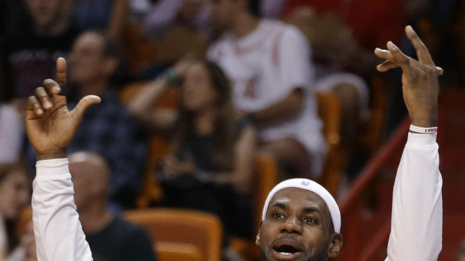 Miami Heat's LeBron James reacts after Ray Allen scored and was fouled during the first half of an NBA basketball game against the Golden State Warriors, Thursday, Jan. 2, 2014, in Miami