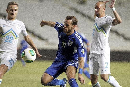 Nektarios Alexandrou, center, of Cyprus controls the ball as Slovenia's Ales Martelj, left, and Miso Brecko make a challenge during their World Cup group E qualifying soccer match at GSP stadium in Nicosia, Cyprus, Tuesday, Sept. 10, 2013