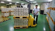 An employee of the Bank of Korea moves packs of banknotes during a photo call at the bank's headquarters in Seoul