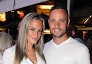 Oscar Pistorius and Reeva Steenkamp at Melrose Arch in Johannesburg last month. A tearful Pistorius has appeared before a South African magistrate were he was formally charged with murdering his model girlfriend on Valentine's Day