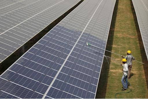 File photo of workers cleaning photovoltaic panels inside a solar power plant in Gujarat