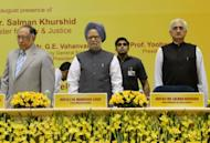 Indian Prime Minister Manmohan Singh (C), flanked by Indian Chief Justice S.H. Kapadia (L) and Union Minister for Law and Justice Salman Khurshid (R), attends a legal conference in New Delhi