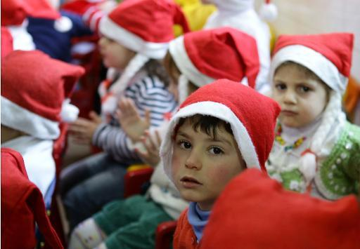 Syrian children wearing red Santa hats take part in Christmas celebrations at a kindergarten in the Syrian capital Damascus on December 19, 2013