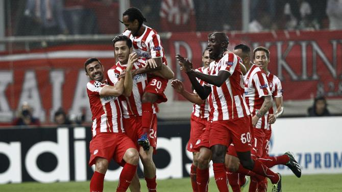 Olympiakos' players celebrate a goal against Benfica during Champions League soccer match in Piraeus near Athens