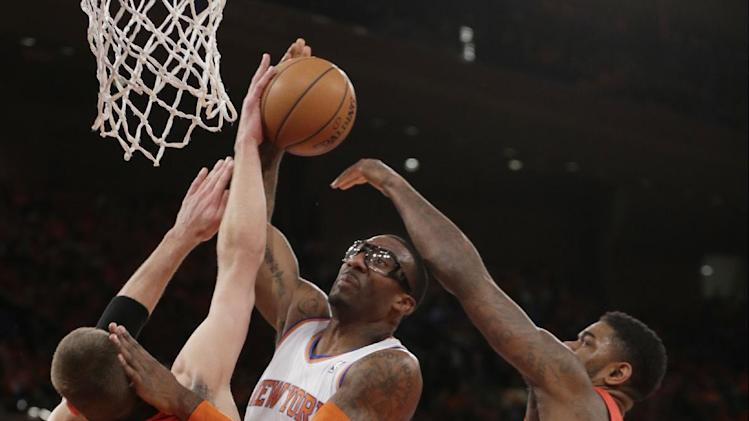 Toronto Raptors' Jonas Valanciunas (17) and Amir Johnson (15) defend New York Knicks' Amar'e Stoudemire during the first half of an NBA basketball game Wednesday, April 16, 2014, in New York