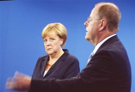 A TV duel of German Chancellor Angela Merkel of the Christian Democratic Union (CDU) with her challenger, the top candidate of the Social Democratic Party (SPD) in the upcoming German general elections Peer Steinbrueck, is shown on a screen in Berlin, September 1, 2013. REUTERS/Fabrizio Bensch