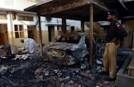 A Pakistani policeman stands next to the wreckage of a burnt car at a school that was set fire by an angry mob, following a protest alleging the school gave a test that insulted the Prophet Mohammed, in Lahore on November 2, 2012. Blasphemy is an extremely sensitive issue in Pakistan, where 97 percent of the population are Muslims
