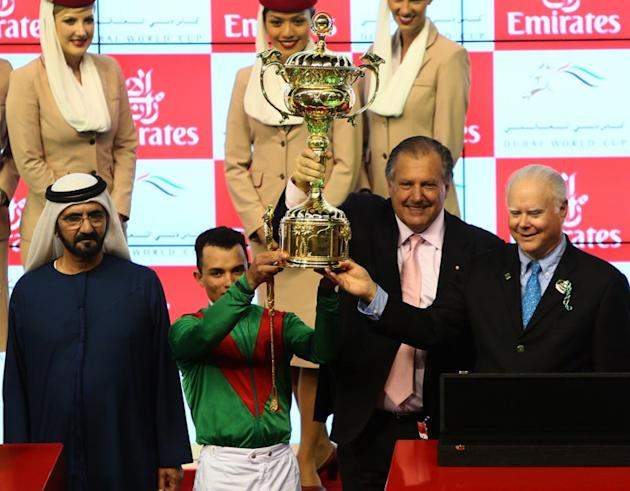 Jockey Joel Rosario and the Austrailain owners (R) of Animal Kingdom, raise the trophy along with the ruler of Dubai Sheikh Mohammed Bin Rashid al-Maktoum (L) after winning the $10 million Dubai World