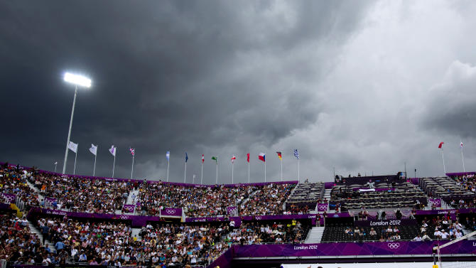 Rain clouds gather as dancers entertain spectators at the Horse Guards Parade before a Beach Volleyball match in London