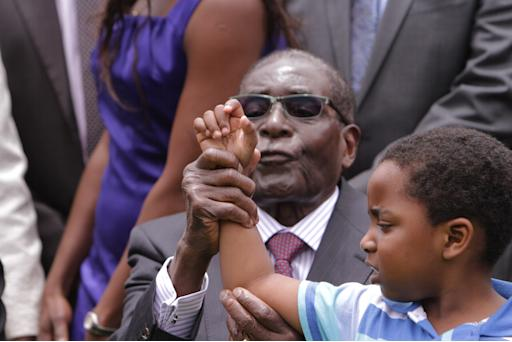 Zimbabwean President Robert Mugabe  attempts to make Dali Thando Phekezela Mphoko, the grandson of  his Deputy President, Phekezela Mphoko, chant the party's slogan after the swearing in ceremony at State House in Harare, Friday, Dec, 12, 2014. Mphoko was sworn  in following a cabinet reshuffle that saw former deputy President Joice Mujuru dismissed from her post, over allegations that she plotted to remove the Zimbabwean President from power. (AP Photo/Tsvangirayi Mukwazhi)