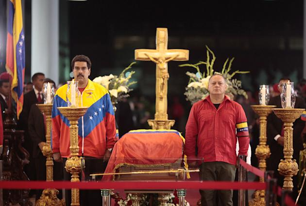 In this photo released by Miraflores Press Office, Venezuela's interim President Nicolas Maduro, left,  and Diosdado Cabello, President of Venezuela's National Assembly stand next to the flag-draped c